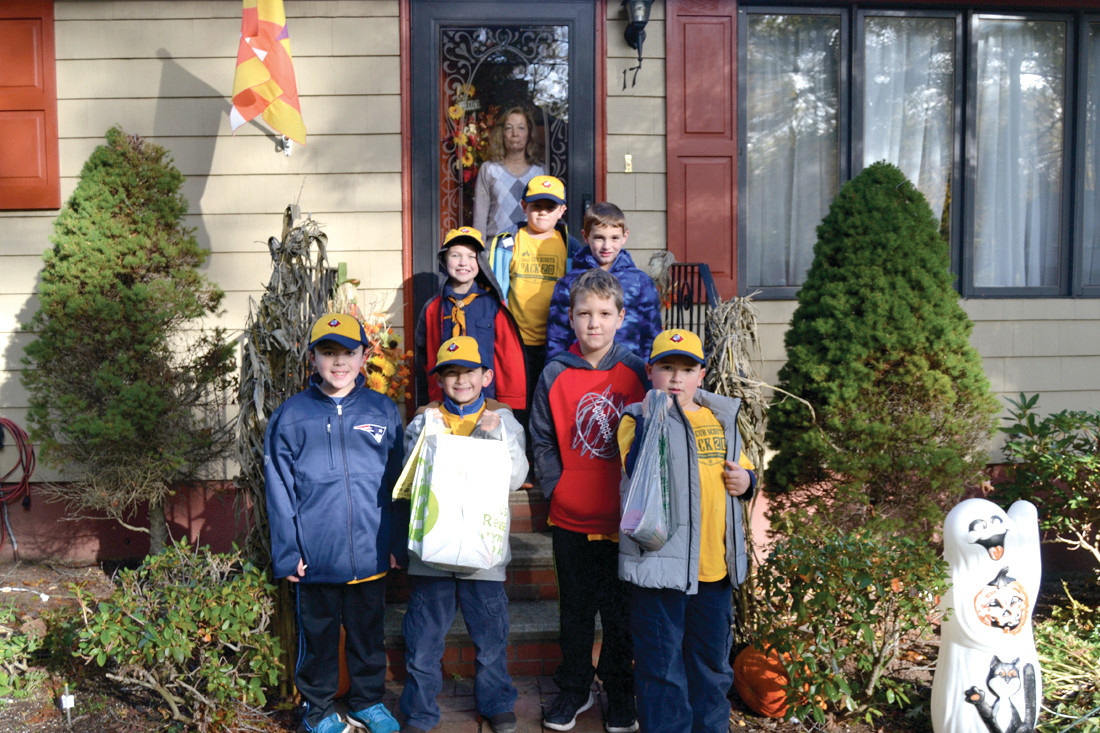 DONATIONS AND MORE: Cub Scouts pick up food donations from the Calestino residence. Along with providing bags of food donations, the Calestinos gave each of the scouts a full-sized candy bar left over from Halloween.