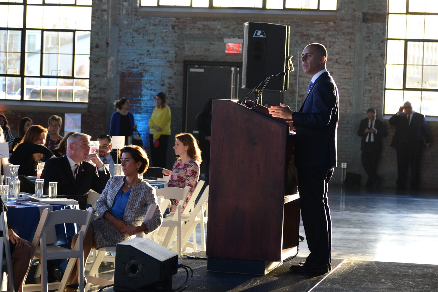 Warwick Mayor Scott Avedisian, Governor Gina Raimondo and Providence Mayor Jorge Elorza (at podium) at the award ceremony at the WaterFire Arts Center.