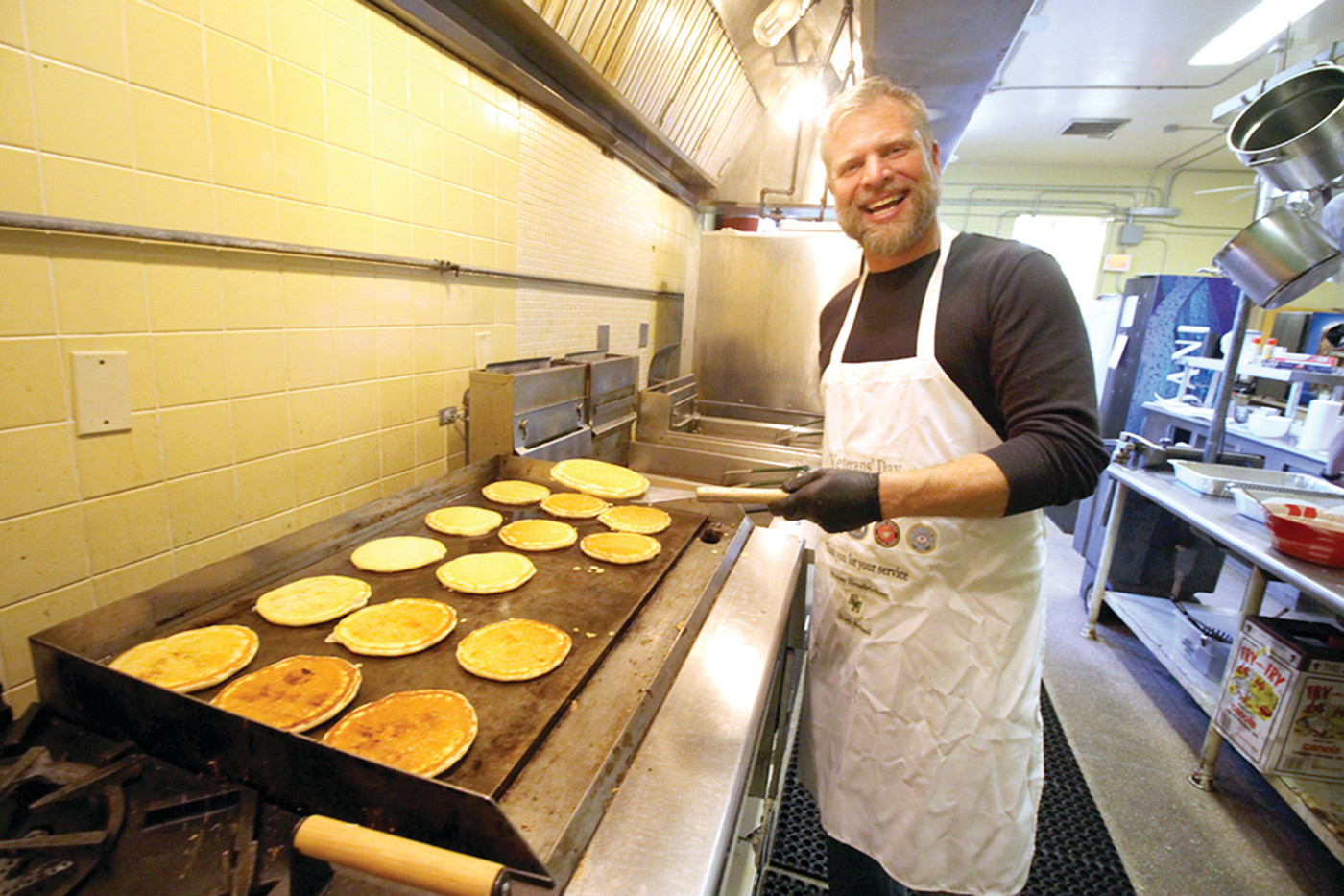 HE DIDN'T FLIP OUT: Jason Pariseau mans the grill at the second annual pancake breakfast at Hendricken Friday morning.