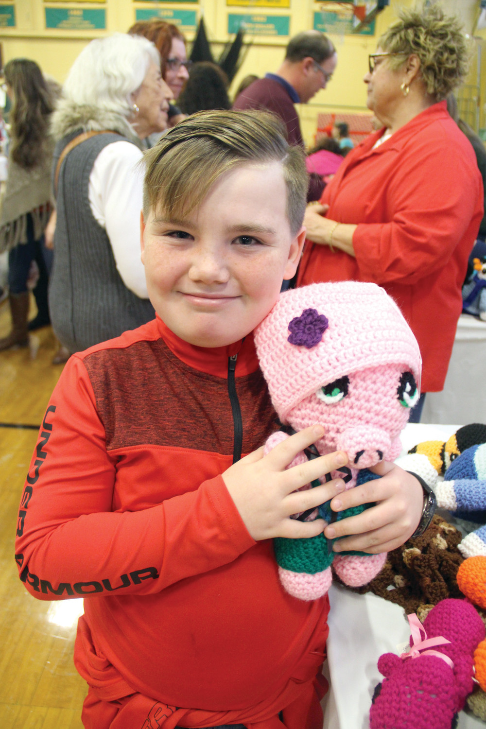 EARLY SHOPPING: Dylan Maddalena picked out a knit pink hat for his baby cousin. He tried it out on a stuffed pink pig to see if it might fit.