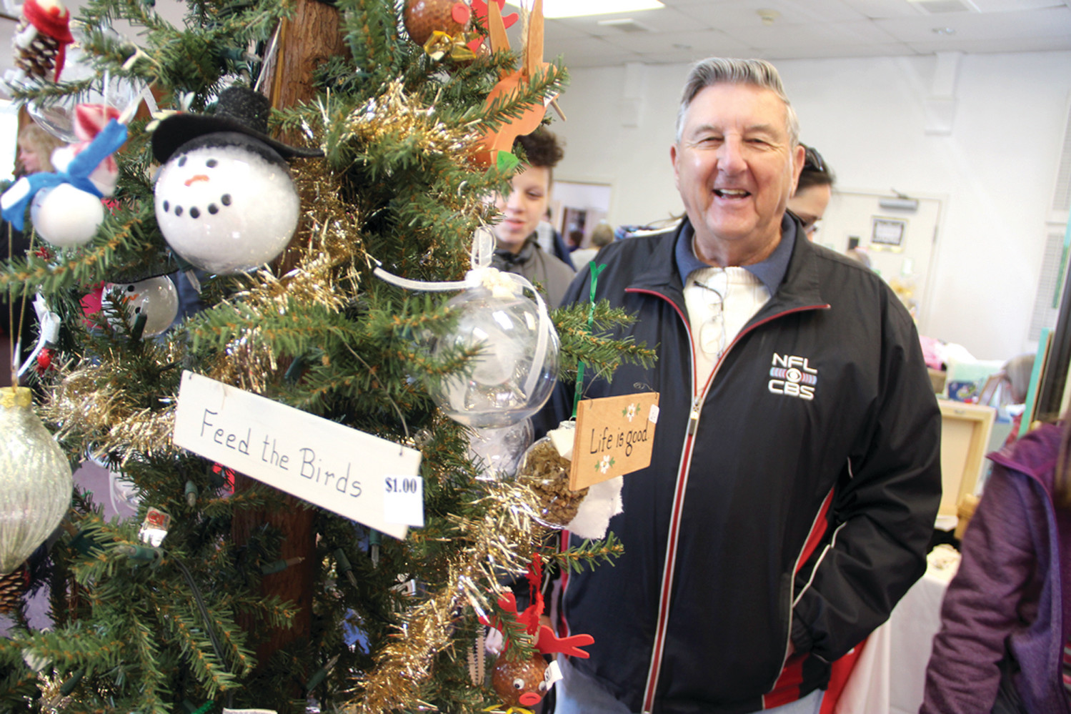 "HE WOULDN'T MISS IT: Graham Mann, who moved to Connecticut this year was sure to return for the church annual bazaar. ""I wouldn't miss it,"" he said. And just in case he might forget, he found a tree decorated with friendly reminders including, ""Feed the birds."""