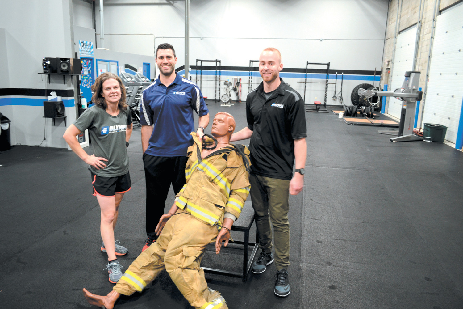 TRAINING FOR DUMMIES: Maura J. Zimmer (NSCA), Olympia Fitness owner Steve Zarriello (CSCS, TPI certified) and Mike Lefebvre pose with their workout dummy, which helps prepare potential firefighter recruits for the final stage of the PPA physical fitness examination.