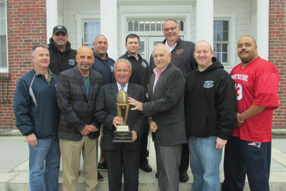PRIZED POSSESSION: North Providence Mayor Charles Lombardi (third left) is all smiles while holding the Fire Bowl Trophy his firefighters have won in three straight years vs. the Johnston Firefighters and he joked with Mayor Polisena about keeping the award after Saturday's game. Also taking part in Tuesday's press conference were (in front) John Laurie, Keith Calci and Adam Barros, (top) Jon Pistacchio, Anthony Rampone, Craig Levesque and Chief Tim McLaughlin.                                                                                                   (Sun Rise photo by Pete Fontaine)