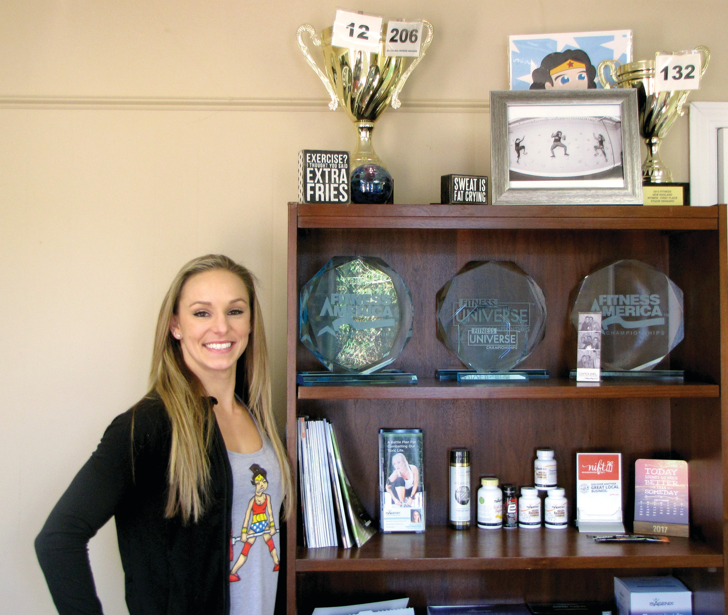 A WINNER'S POSE: Stacie Venagro smiles big next to her fitness competition awards in the office of her Cranston gym.