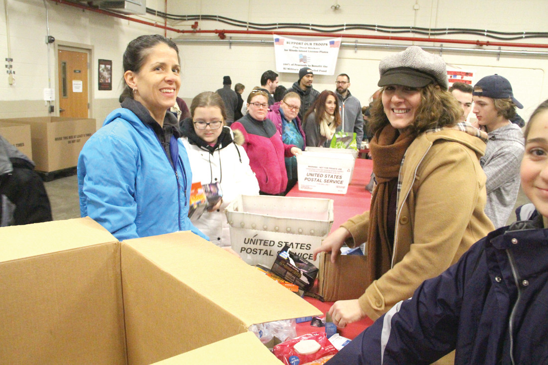 A TEAM EFFORT: Christine Tirocchi and Eva Sasa and members of the Savvy Showmen 4H Club of Foster helped sort donations on Saturday that would be boxed the following day by more volunteers.