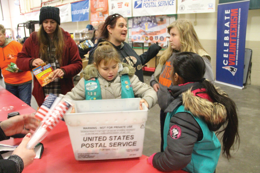A TROOP HELPING TROOPS: Girl Scout Troop 528 from West Warwick helped with the sorting of donations. Scouts Haylie Pelletier and Harini Senthilkumar are in the foreground. Amanda Roberts, leader, and Madison Hoppman are in the back.