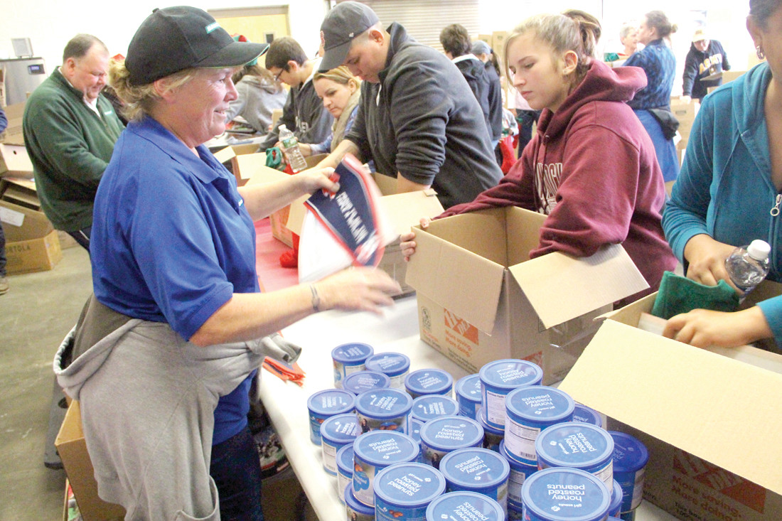 LOVES VOLUNTEERING: Chris Royal of Warwick spent her Sunday morning helping fill more than 500 boxes that will go to service men and -women who won't be home for the holidays.