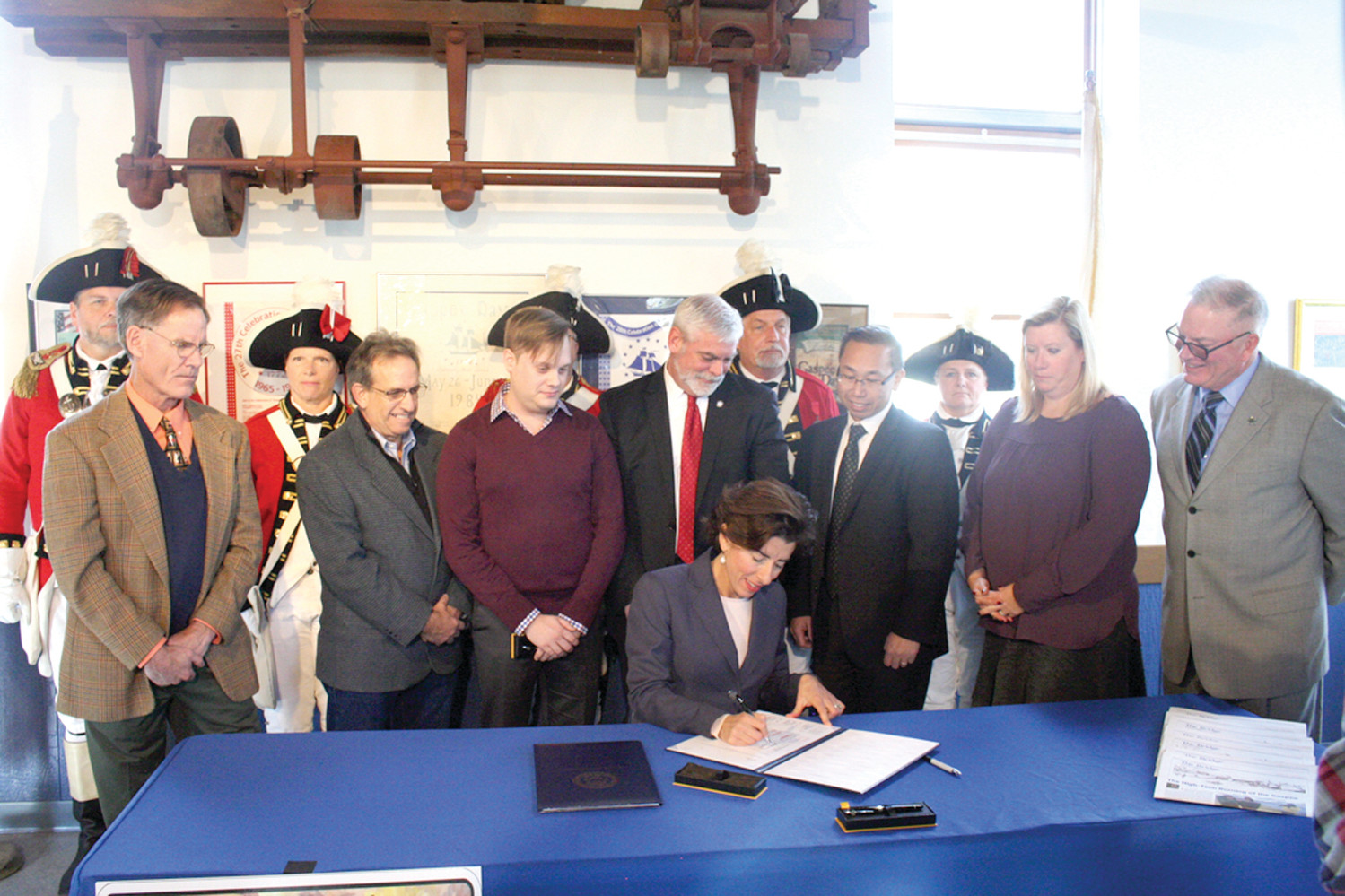 POWER OF THE PLATES: Flanked by Pawtuxet Rangers and watching Governor Raimondo sign the Gaspee Days License Bill are (from left) Councilman Rick Corley, Senator Jim Miller, Gaspee Committee President Ryan Giviens, Mayor Avedisian, Mayor Fung, Senator Lynch Prata and Representative McNamara.