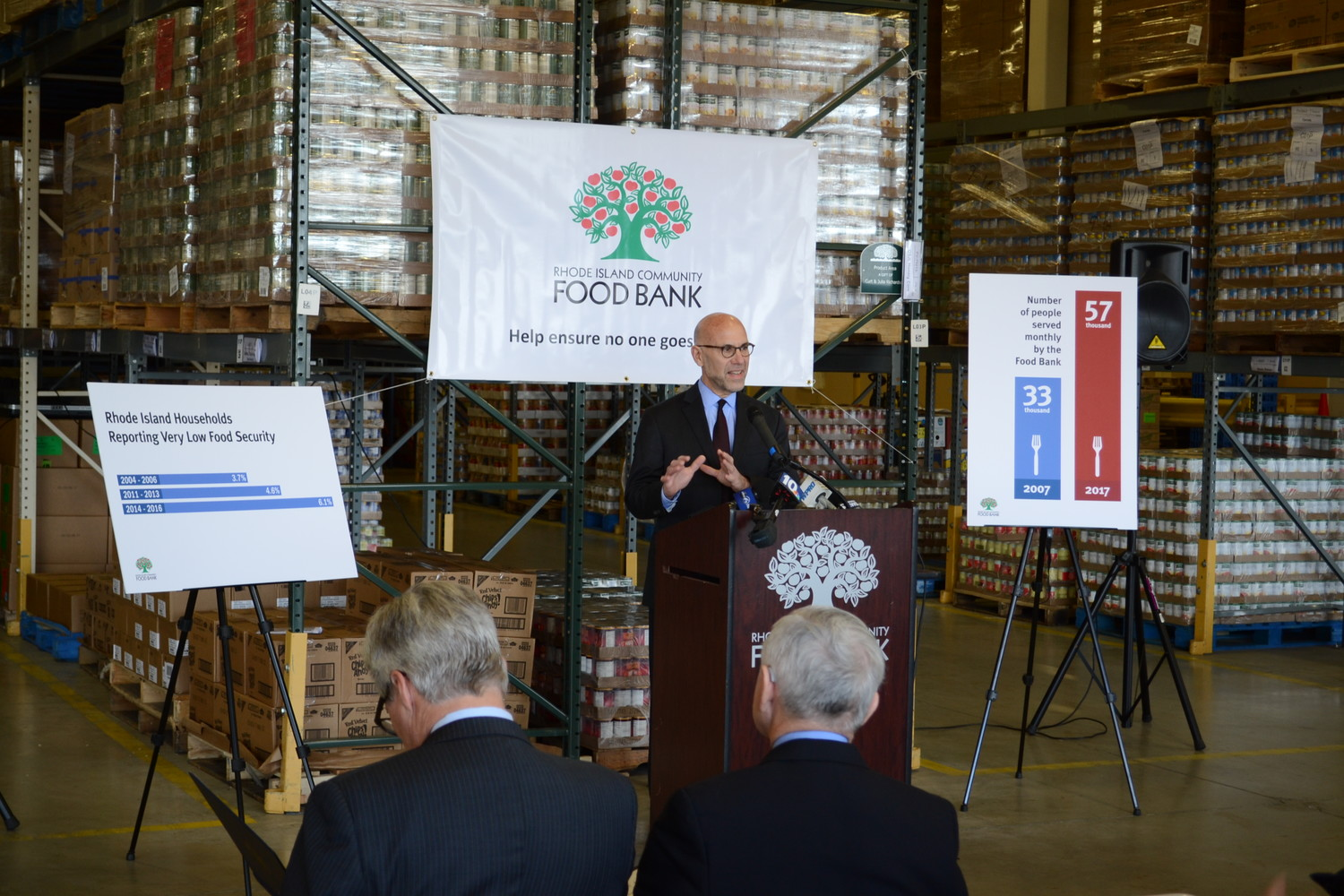 ASSESSING THE SITUATION: Rhode Island Community Food Bank CEO Andrew Schiff speaks at the unveiling of the annual status report on hunger in Rhode Island. Senators Jack Reed and Sheldon Whitehouse are seen in the foreground.