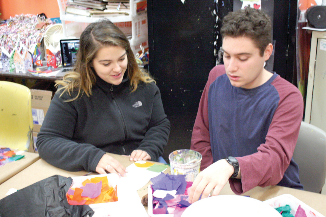 LENDING A HAND: Student-volunteer Jess helps out artist Ryan with his project.