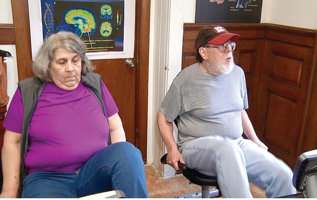 "DAILY ROUTINE: Leslie Smith and Edward Sousa use Brain in Play's recumbent bikes at Pawtucket's Living Well Day Care to partake in ""best practices"" that increase cognitive function, according to the foundation."
