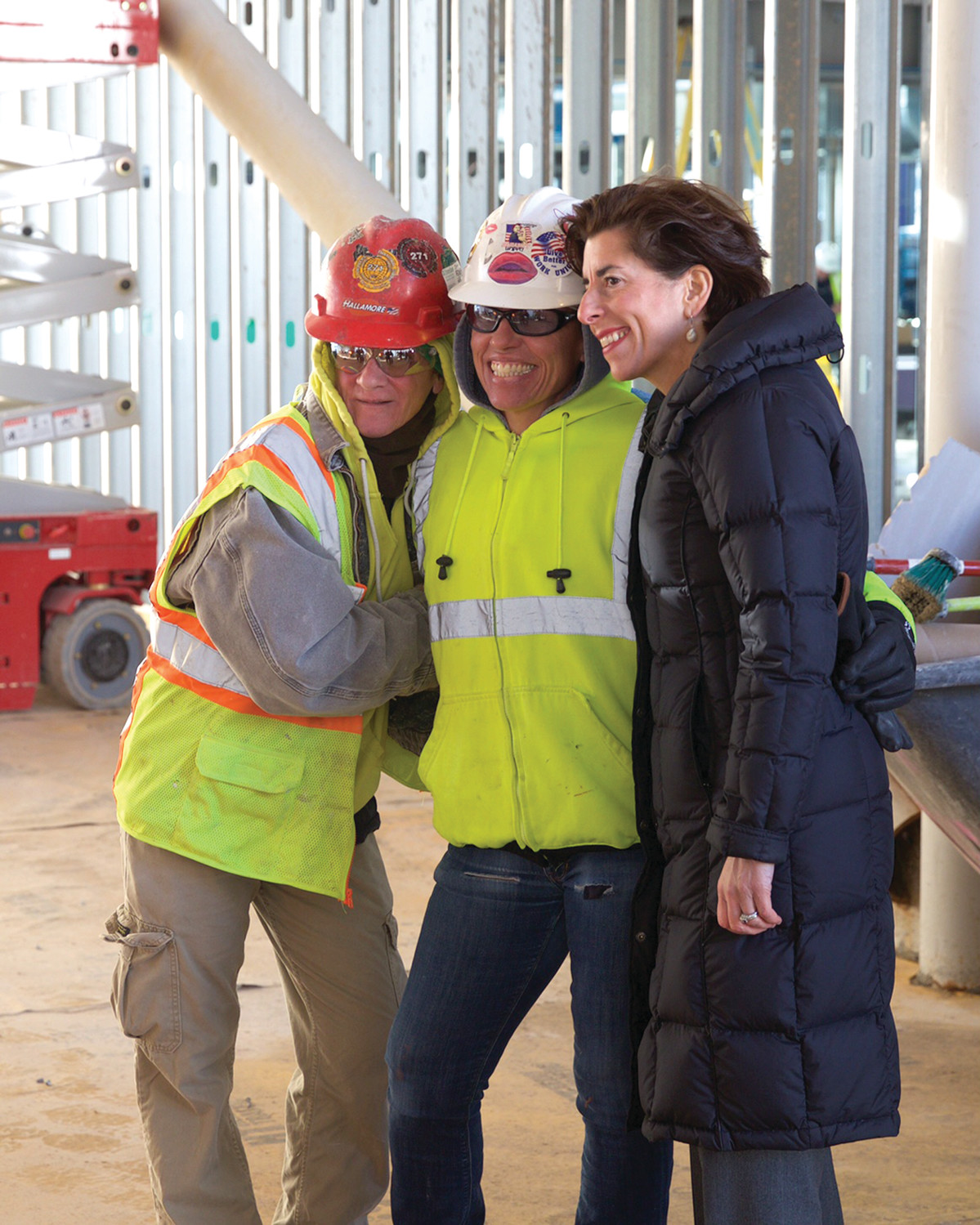 ALL SMILES: Governor Raimondo with some of the workers working on the site.