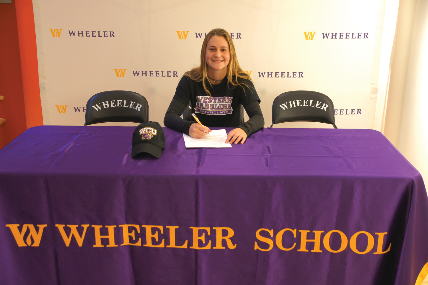 SIGN HERE: Above, Wheeler School's Julia Pezzuco of Johnston gets ready to sign her National Letter of Intent to play women's tennis at Western Carolina University.