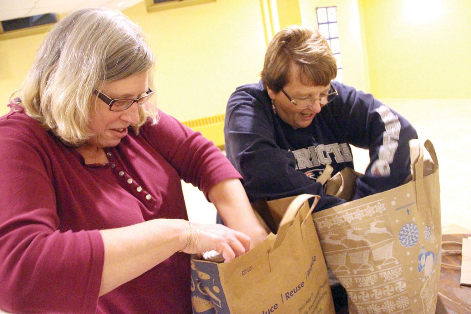 WHAT GOES IN FIRST: Juliette Demers and pastoral minister Cheryl Berube place canned goods in the bottom of bags that were next filled with produce, bread and boxed goods.