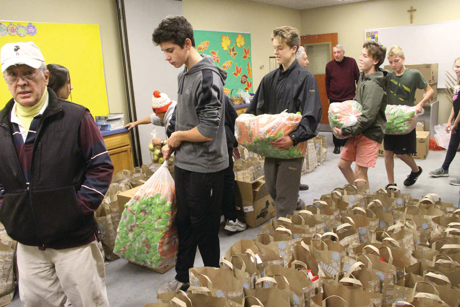 PUTTING IT ALL TOGETHER: Assembly line tactics came into play Monday as St. Gregory the Great Church parishioners packed 150 food baskets for needy families.