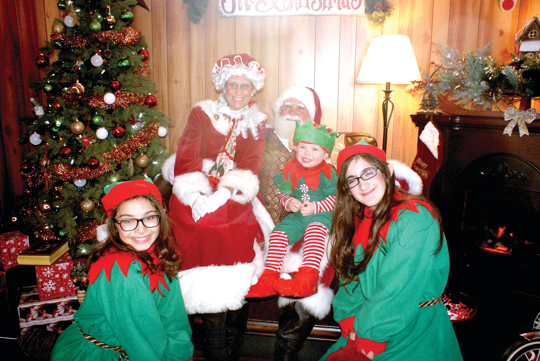 SANTA AND COMPANY: Pictured with Santa Claus is Mrs. Claus along with Elves Twinkie and Perky with Baby Elf, Anthony, on Santa's lap.