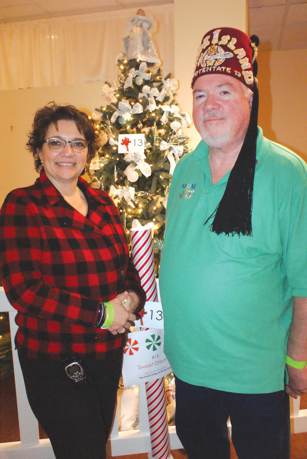 LEADERSHIP: Pictured is Paula Cardi, event coordinator along with Potentate Robert J. O'Brien in front of one of the trees at The FEZ-tival of Trees which was donated by The Grand Lodge of RI.