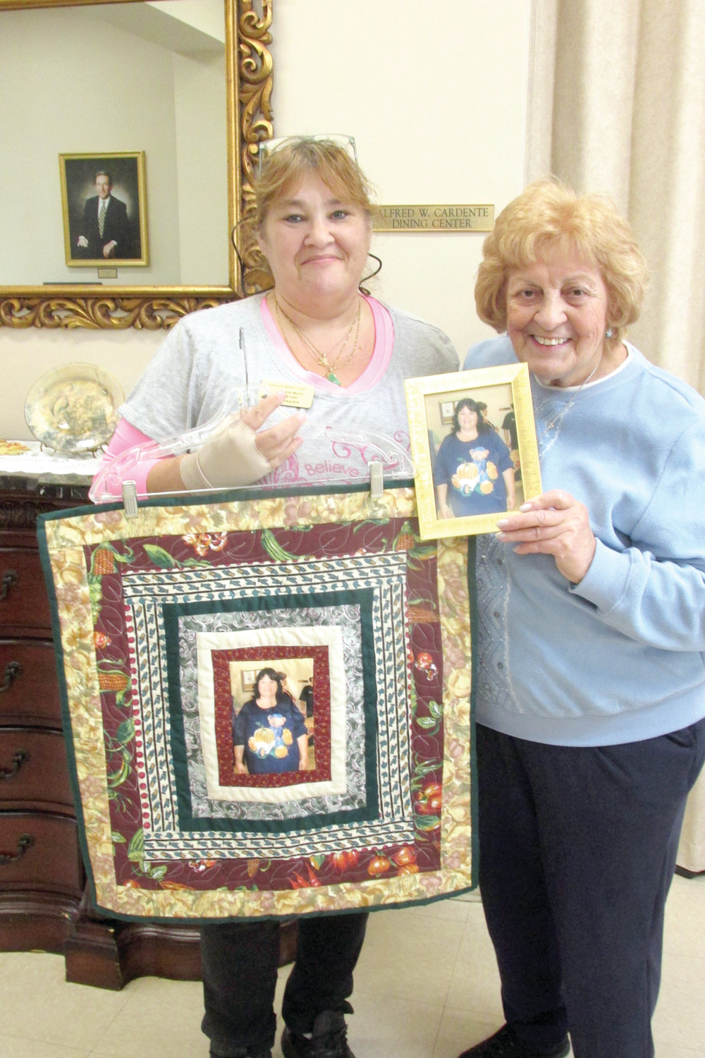 SURPRISE, SURPRISE: Brenda Martin (left), the Dietary Manager at the Johnston Senior Center, holds a specially-made quilt she received from the Quilt Club during a recent ceremony. She's joined by Marie Lanzi, who holds Martin's picture the group used while the making the colorful piece. (Sun Rise photo by Pete Fontaine)