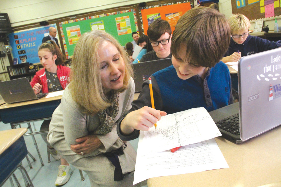 ROBERTSON VISIT: Deputy Commissioner of Education Mary Ann Snider looks on as sixth grader Michael uses his math skills and coordinates to locate Rhode Island cities and towns.
