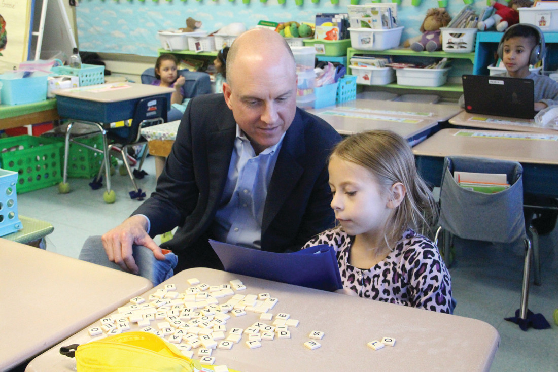 SPELLING IT OUT: Commissioner Ken Wagner looks on as Robertson School first grader Mia Santos selects letters to spell words. With each letter Mia selected, Wagner asked her to sound out the letter. She didn't disappoint him.