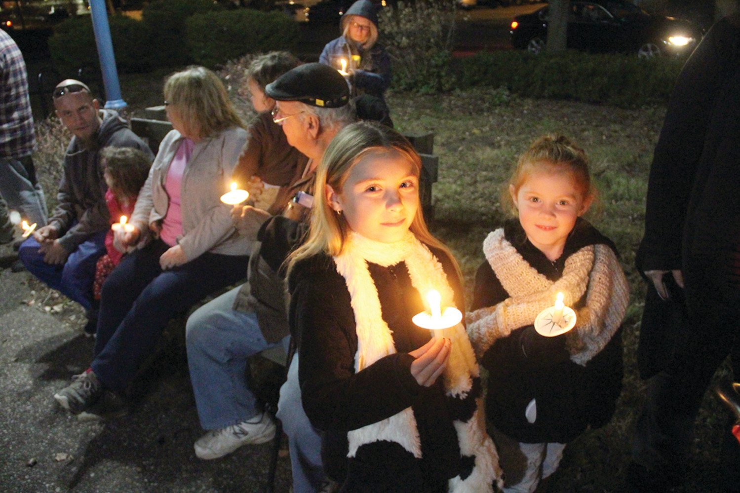 CANDLE GLOW: People joined in singing Christmas carols following the lighting of the Conimicut Village tree Friday evening.