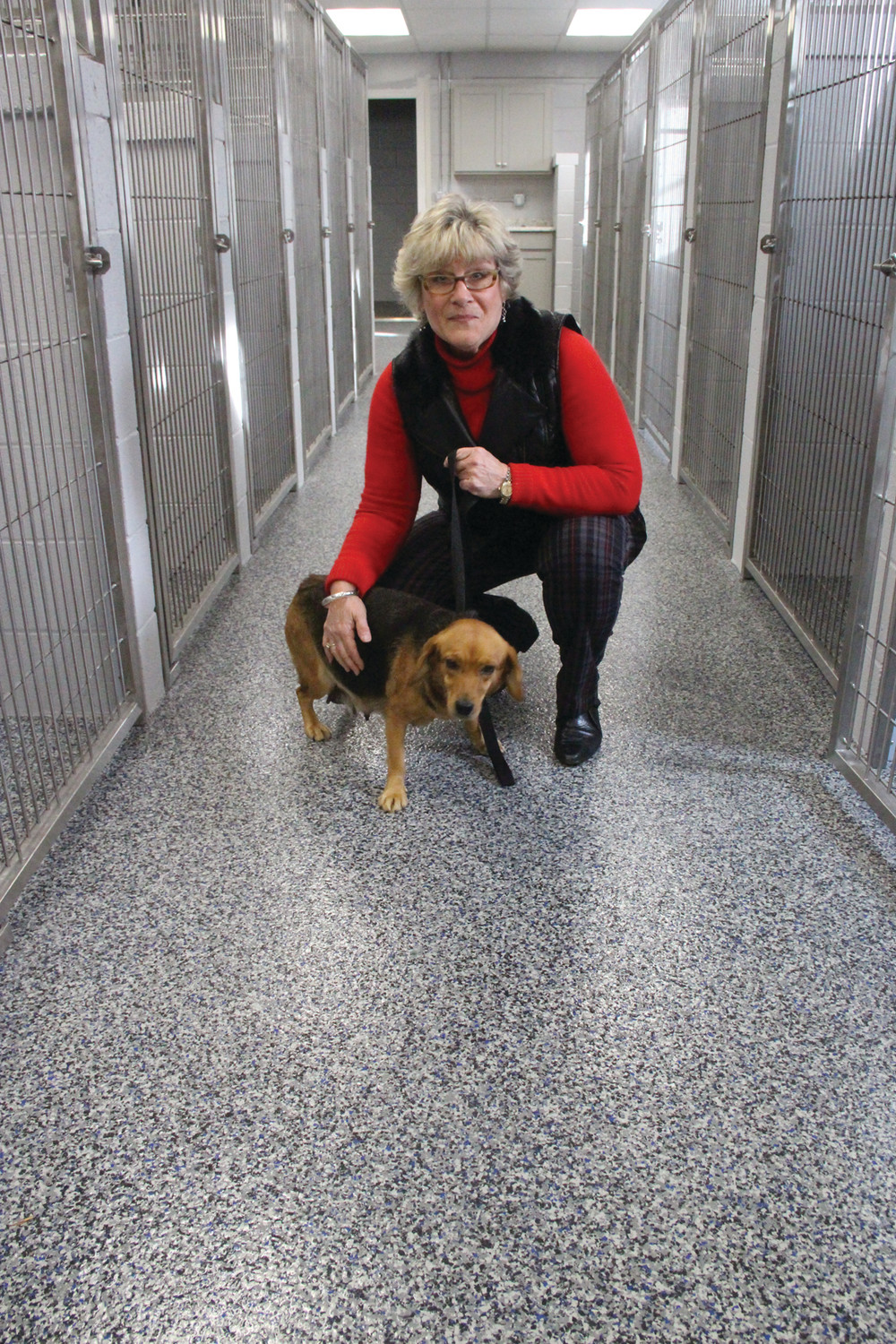 CHECKING IT OUT: Patti Reppucci, who has volunteered at the league for several years, takes a recent rescue for a look-see of the new facilities. The dog is staying with a foster family until it has a home.