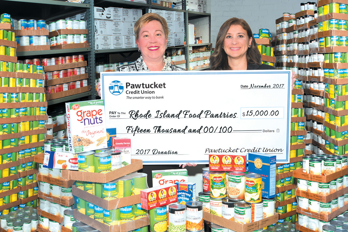 A HELPING HAND: Donna Gregson (left), EVP/Retail Administration, and Paola Fernandez, AVP/Community Outreach, present a $15,000 grant to local area food pantries.