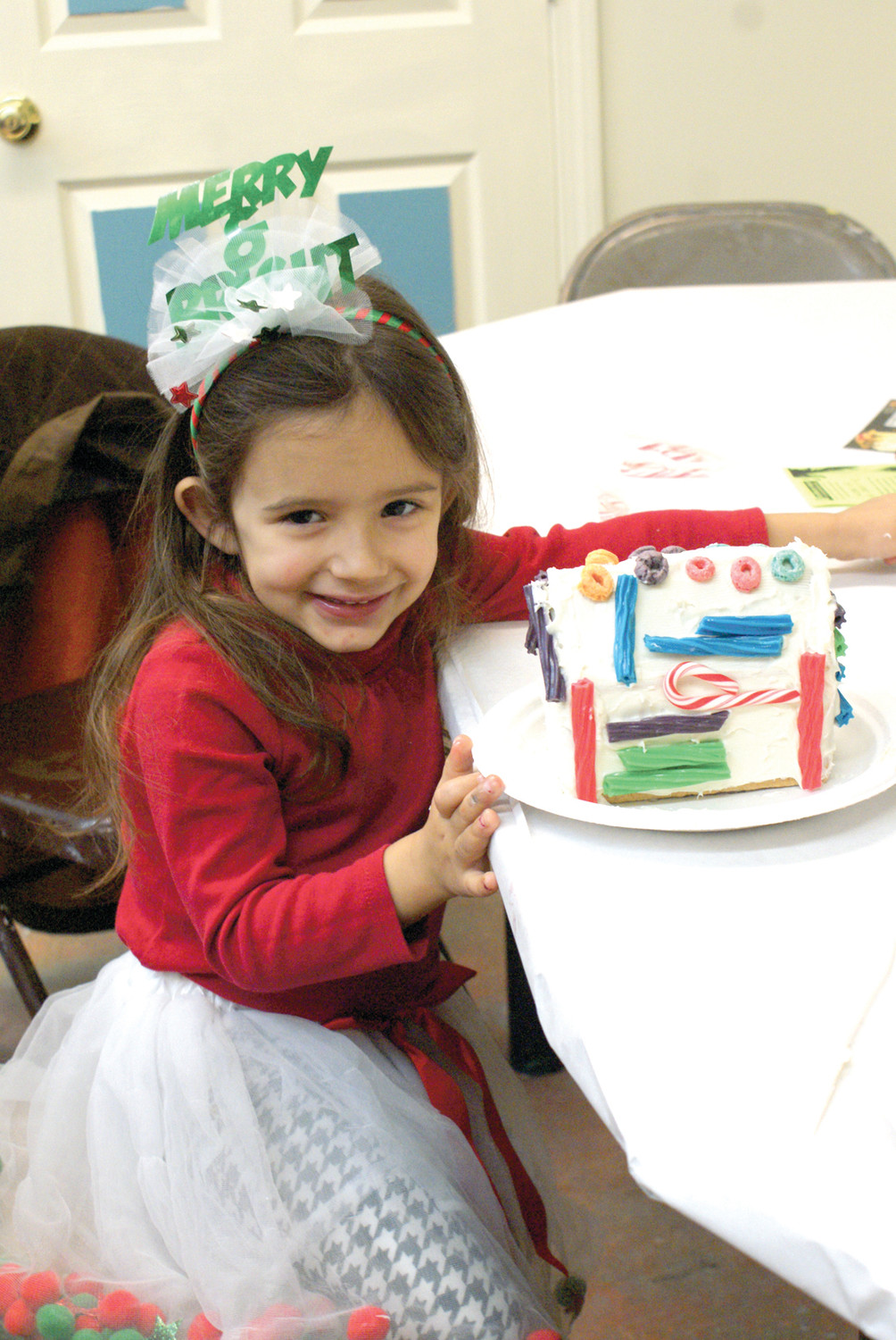 HOW SWEET IT IS: Olivia Rapoza, age 3, is seen with her completed Gingerbread House during the 13th Annual Gingerbread Decorating Contest as the Artists' Exchange this past Saturday.