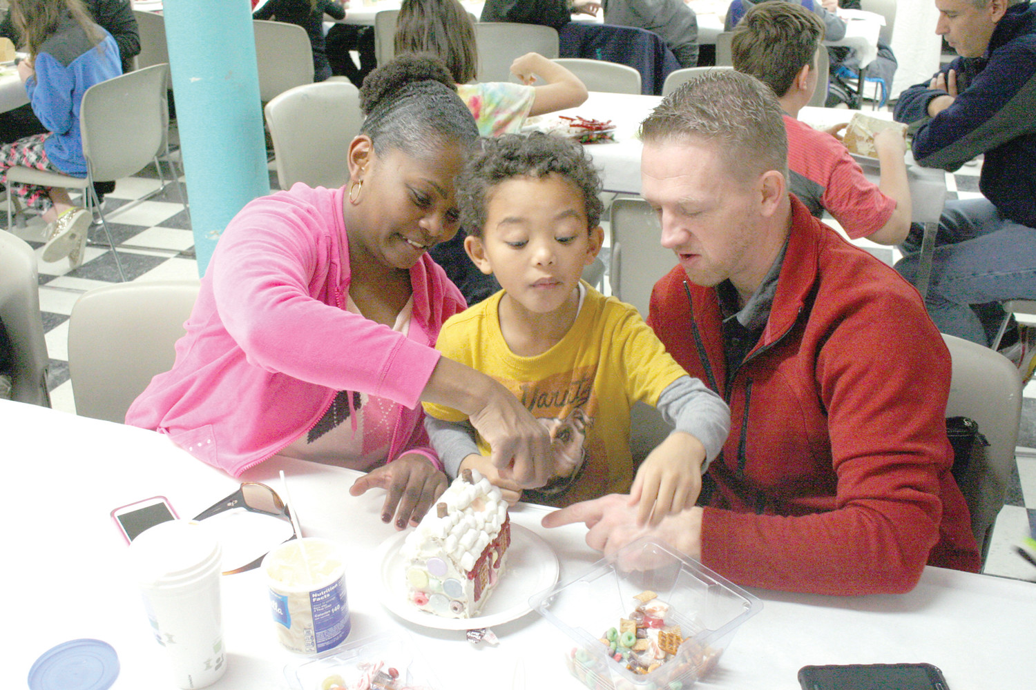 QUITE THE HANDFUL: Aydan Gray goes to grab candy – maybe to eat, maybe to decorate with – as he builds his gingerbread house with parents Brian and Ester Gray.