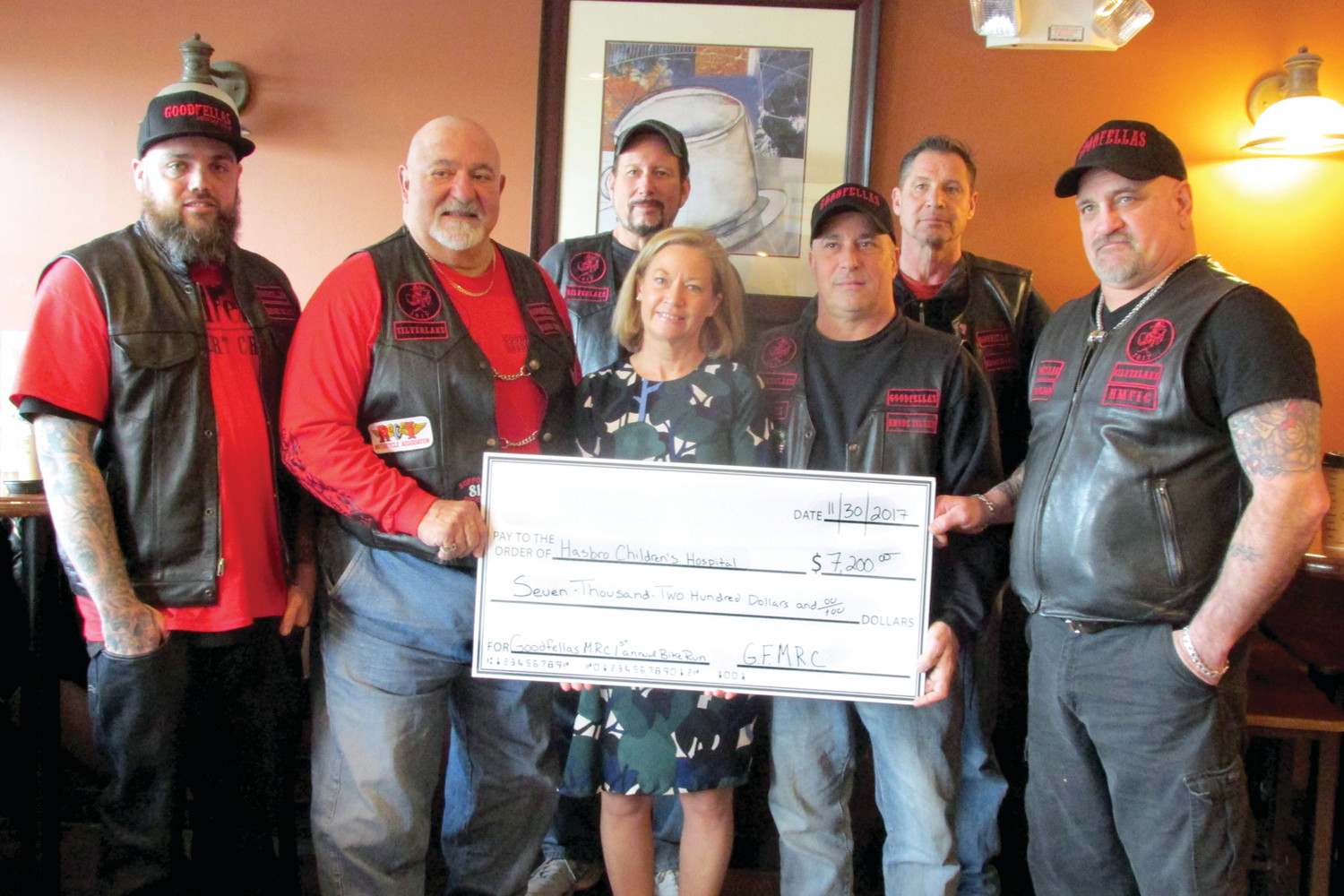 FANTASTIC FOLKS: Michele Branigan, the Senior Major Gifts Officer at Hasbro Children's Hospital, holds a mock check for $7,200 with members of the Goodfellas Motorcycle Club who are, from left: Kurt Stumpf, Cal Calabro, Joe Turchetta, Eugene Benedetti, Jeff Gauch and Lou Pierce. (Sun Rise photos by Pete Fontaine)