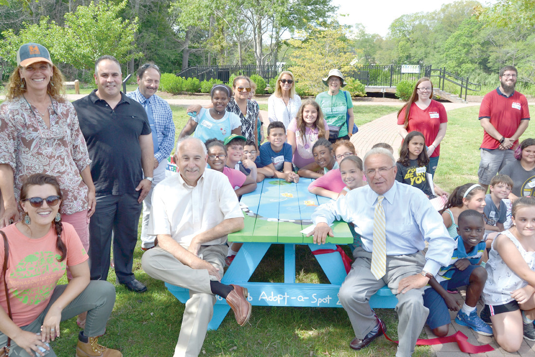 BRINGING COMMUNITIES TOGETHER: Johnston Mayor Joseph Polisena and North Providence Mayor Charles Lombardi join other community leaders and program participants in celebrating the dedication of new picnic tables at Cricket Field.