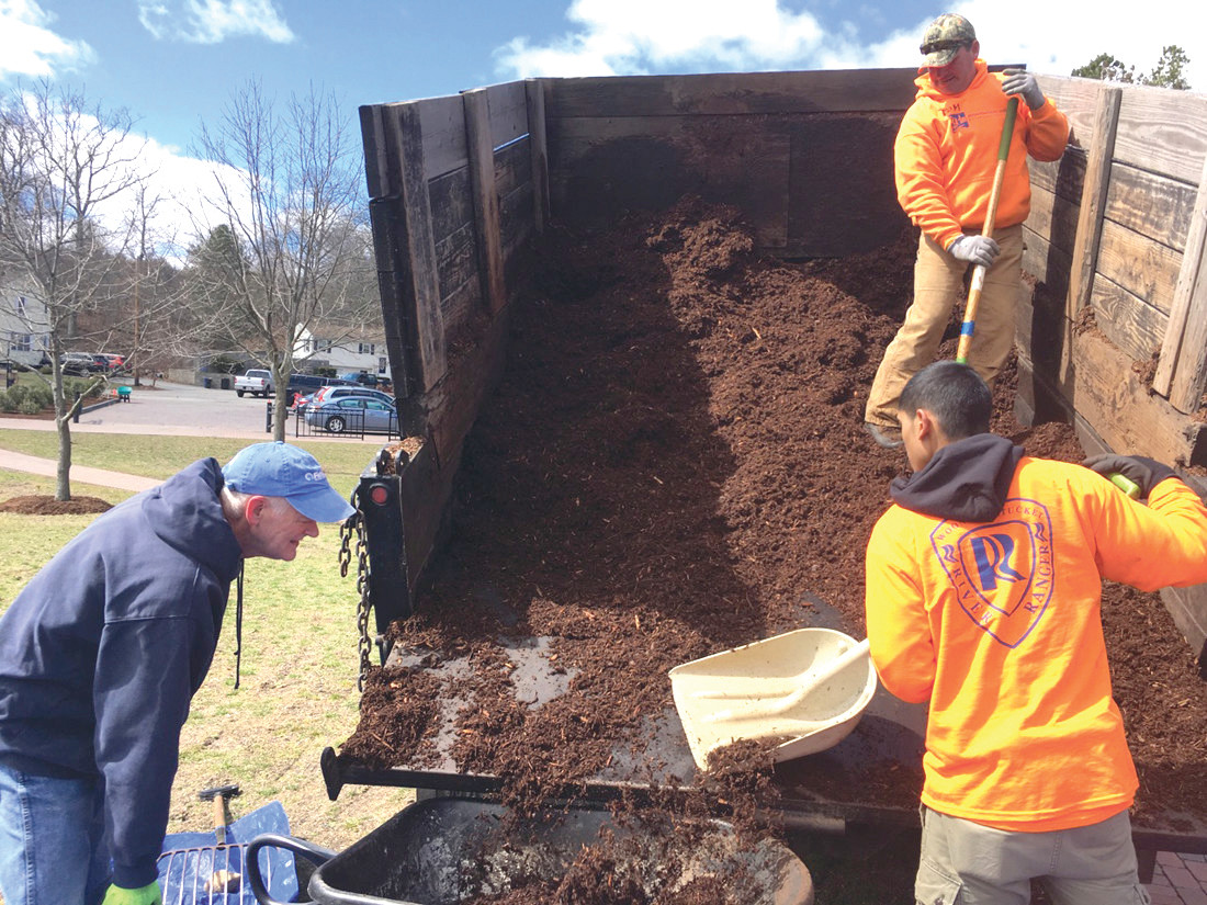 FILL IT UP: John Hake (left), a fishery biologist and vice president of the board of directors of the Woonasquatucket River Watershed Council, gets a load of mulch to spread at Cricket Field in Johnston.