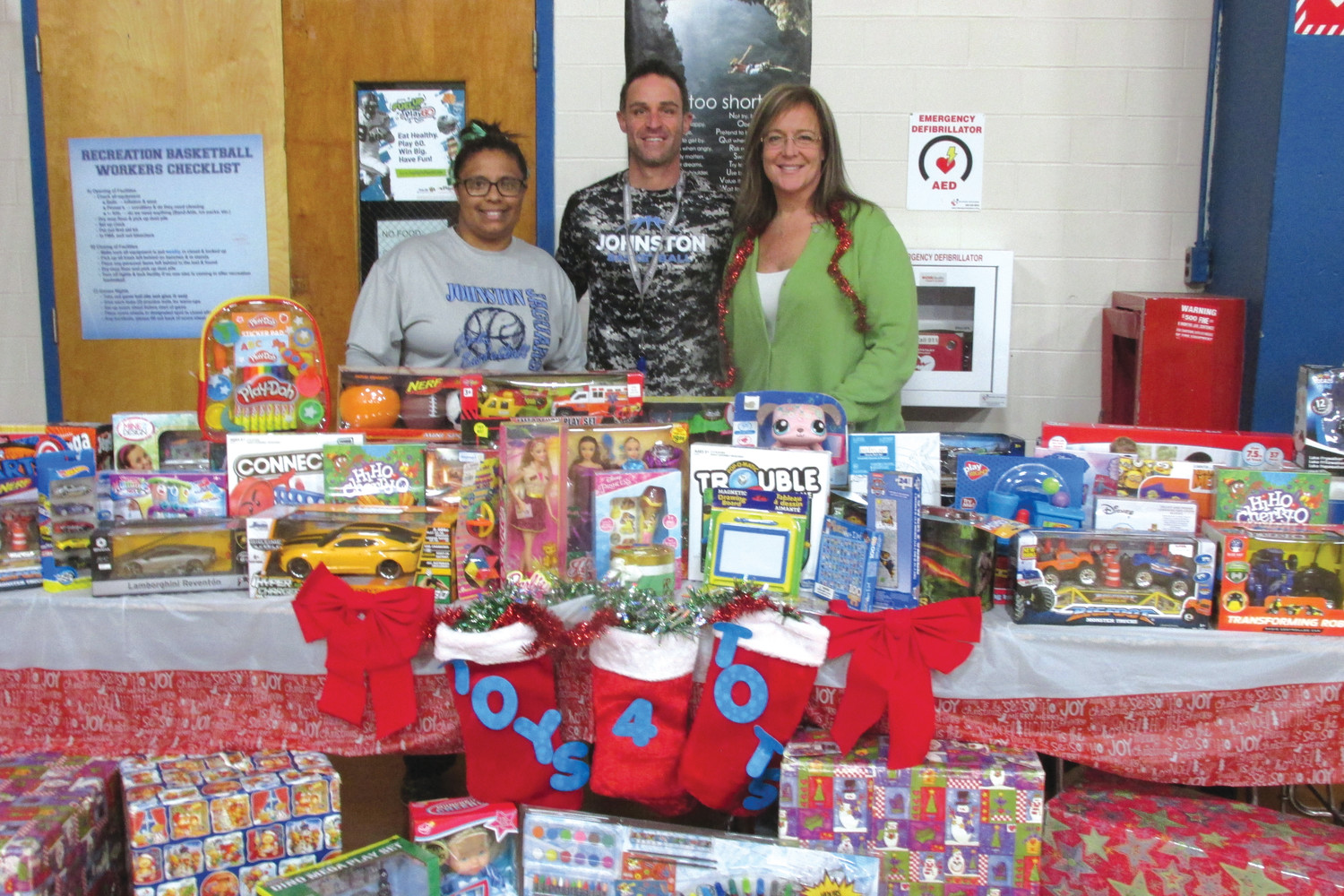 GRAND GIVERS: Gianna Mazzulla, Brian Iafrate and Greta Lalli stand behind just one of the many tables that were topped with toys and games during the Toys for Tots Scrimmage in Johnston.