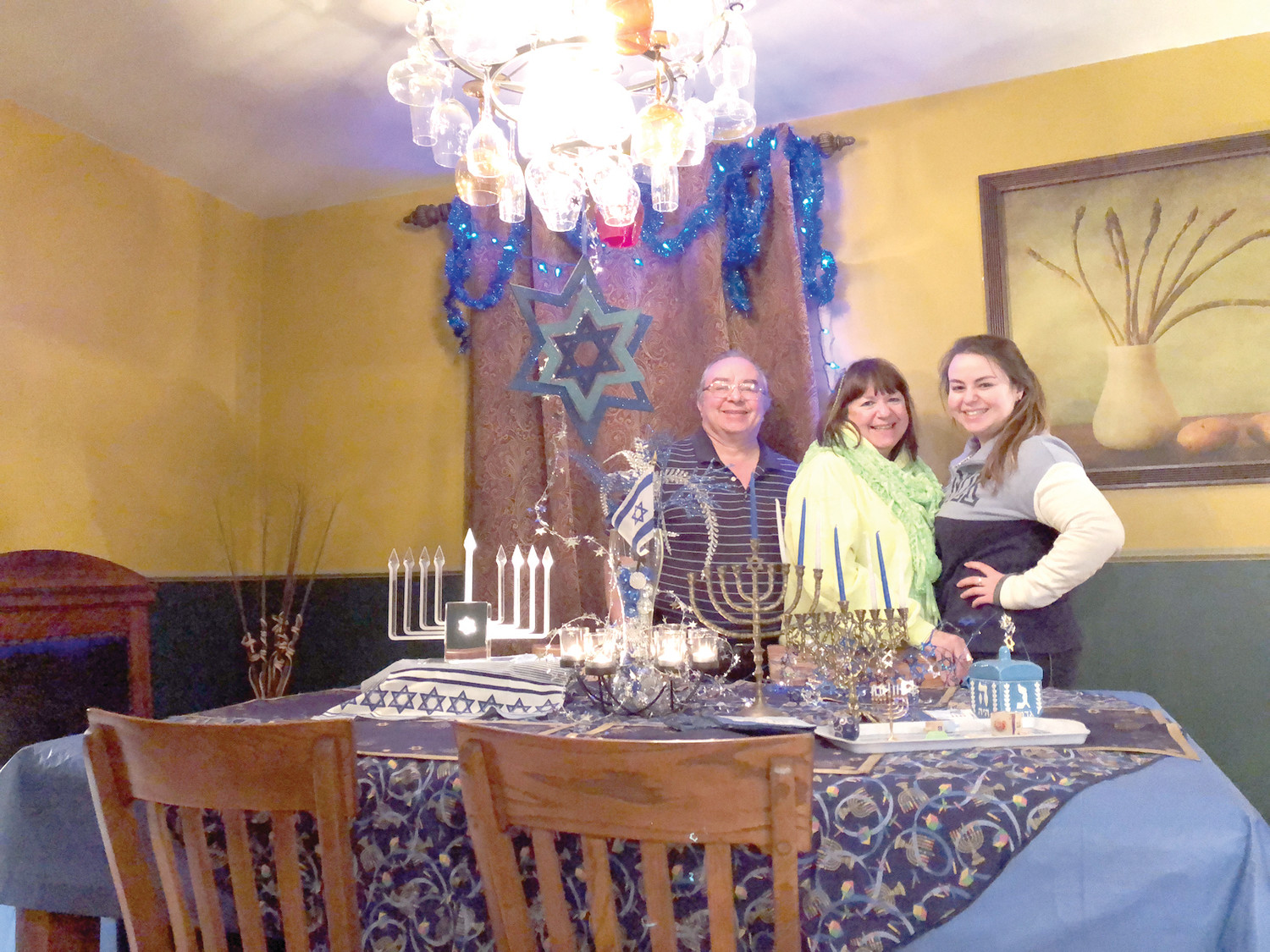 OH, THOSE 8 CRAZY NIGHTS: John, Laura and Sylvia smile as they prepare to light their menorahs in observance of Hanukkah.
