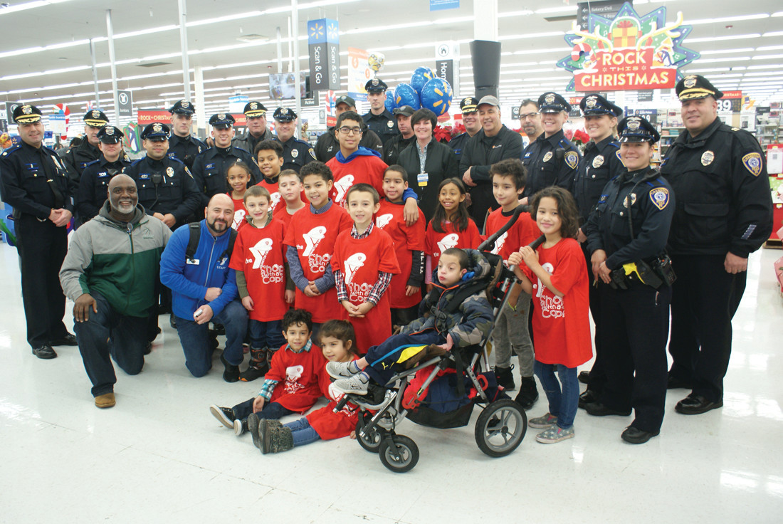 READY TO SHOP: Pictured are some of the children who participated in Shop With A Cop on Dec. 9 at Walmart on Plainfield Pike. Included in the photo are Richard Adamo and Paul Monteiro (Members of the Cadence Charitable Committee), Walmart Store Manager Reagan Cannon, participating Cranston Police Officers, Chief of Police, Col. Michael Winquest and members of they Cranston YMCA Board along with Cory Guglietti who is the Executive Director of the Cranston YMCA.