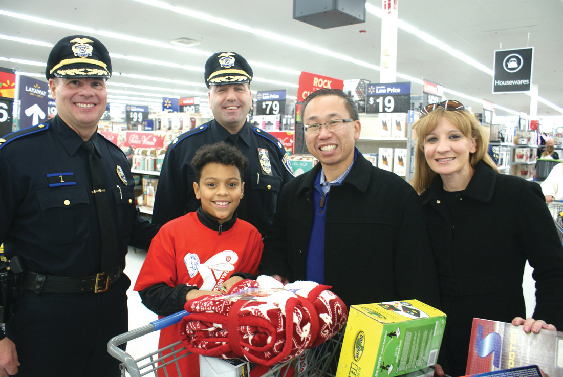 HAPPY SHOPPER: Adreyan Perez got a lot of help with his shopping during Shop With A Cop on Dec. 9 at Walmart on Plainfield Pike. He was joined by Mayor Allan Fung and his wife Barbara Ann Fenton, Col. Michael Winquist (Chief of Police) and Major Todd Patalano.