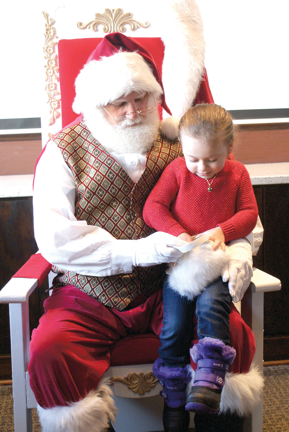CHECKING THE LIST: Santa Claus enjoyed breakfast and time with children at The Corner Bakery in Garden City on Dec. 10. He is pictured with Eliana Valorose, age 3, as he checks her list.