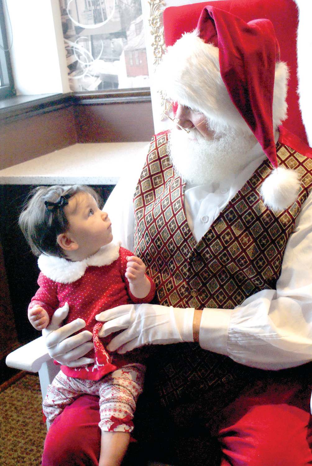 FIRST CHRISTMAS: Meeting Santa Claus for the first time was 7 months old Brinley Fusco at The Corner Bakery. The experience was magical for both Santa and Brinley.