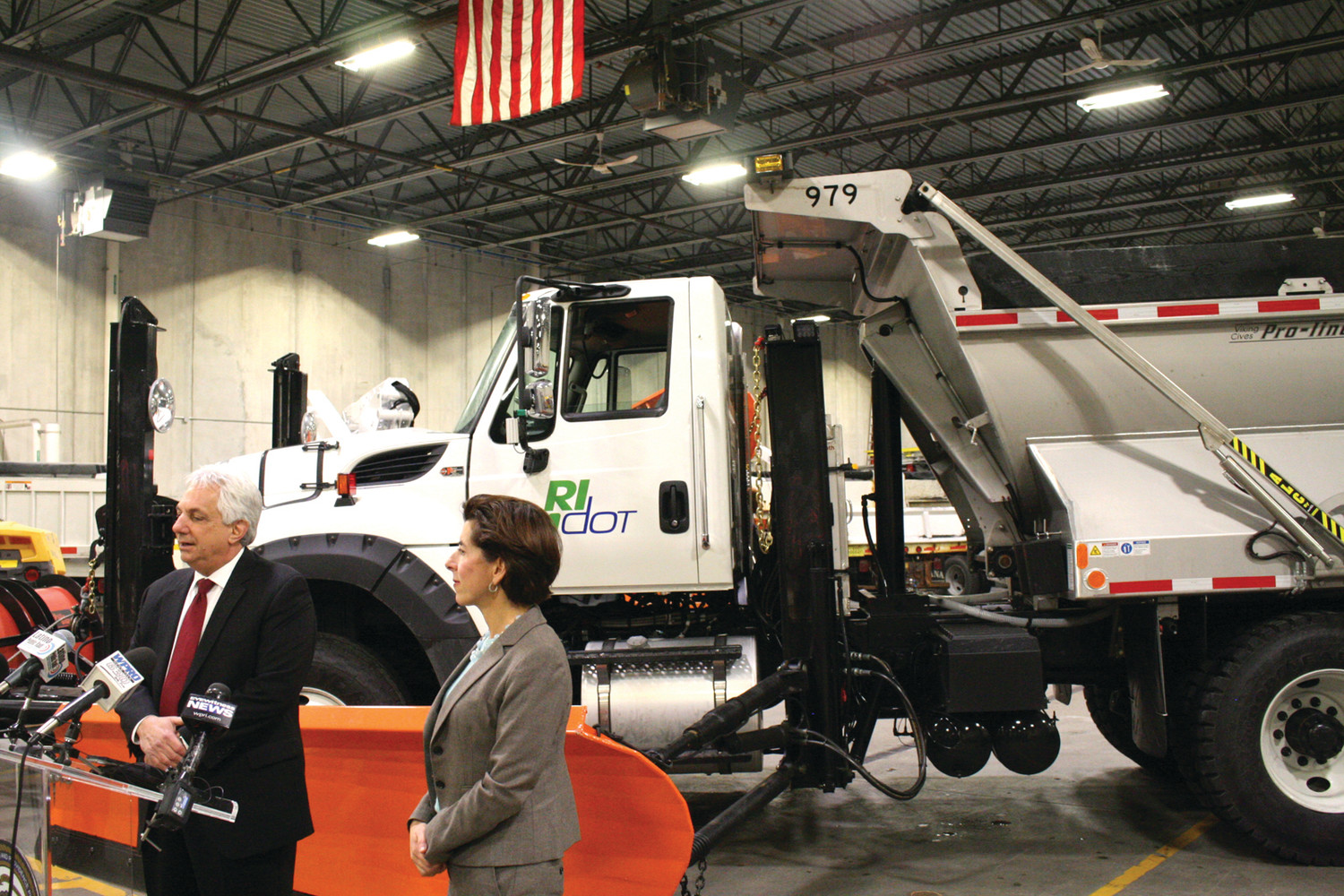 BRAND NEW TRUCKS: Flanked by one of the new state snow plows, Governor Gina Raimondo and DOT Director Peter Alviti Jr. speak to reporters at a DOT garage on Lincoln Avenue in Warwick Tuesday afternoon.