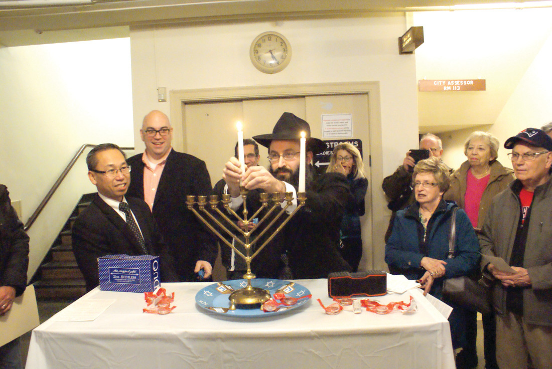 CELEBRATION: Rabbi Yossi Laufer of Chabad of West Bay led the Hanukkah celebration at Cranston City Hall as Mayor Allan Fung and the crowd that gathered joined in.