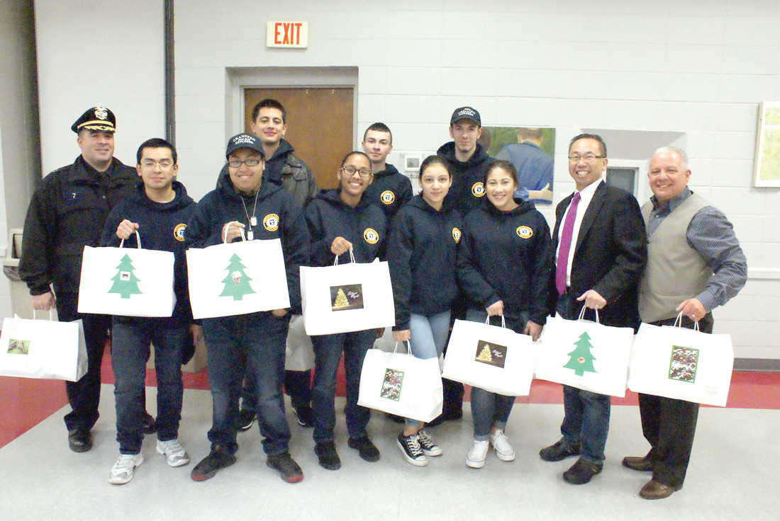 TEAM EFFORT:  Volunteers Cranston Police Cpt. Vincent McAteer and members of his Cranston Police Explorer's Post along with Mayor Allan Fung and Jeffrey P. Barone, Executive Director of the Cranston Department of Senior Services were in the holiday spirit as they were about to leave the Cranston Senior Center with Christmas meals to deliver to senior citizen residents in need.