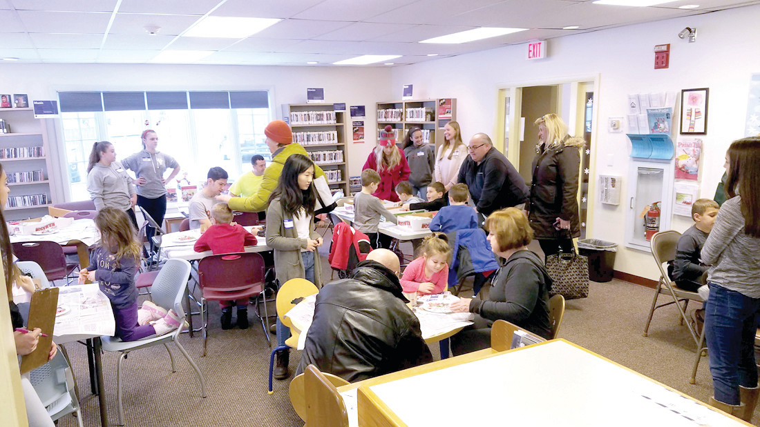 ALL HANDS ON DECK: The Oaklawn Library was overtaken by gingerbread house designers and builders at their first program on Saturday, December 16.