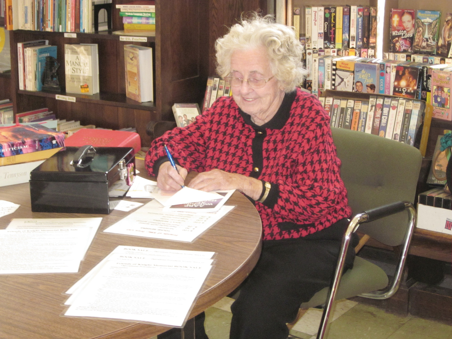 SPEAK SOFTLY AND CARRY A BIG SMILE: Harriet Dever, doing what she loved best, giving back to her community. She is diligently working on the Book Sale at her cherished Knight Memorial Library in 2014.