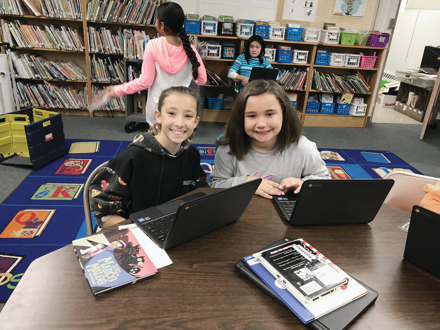 BEAMING FROM DEVICE TO DEVICE: Dutemple Elementary students show their coding prowess during library period.