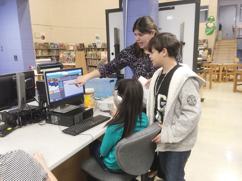 COACHING EM UP: Edgewood Elementary school librarian Kather Tanner shows the 5th graders the newest Minecraft coding challenge.