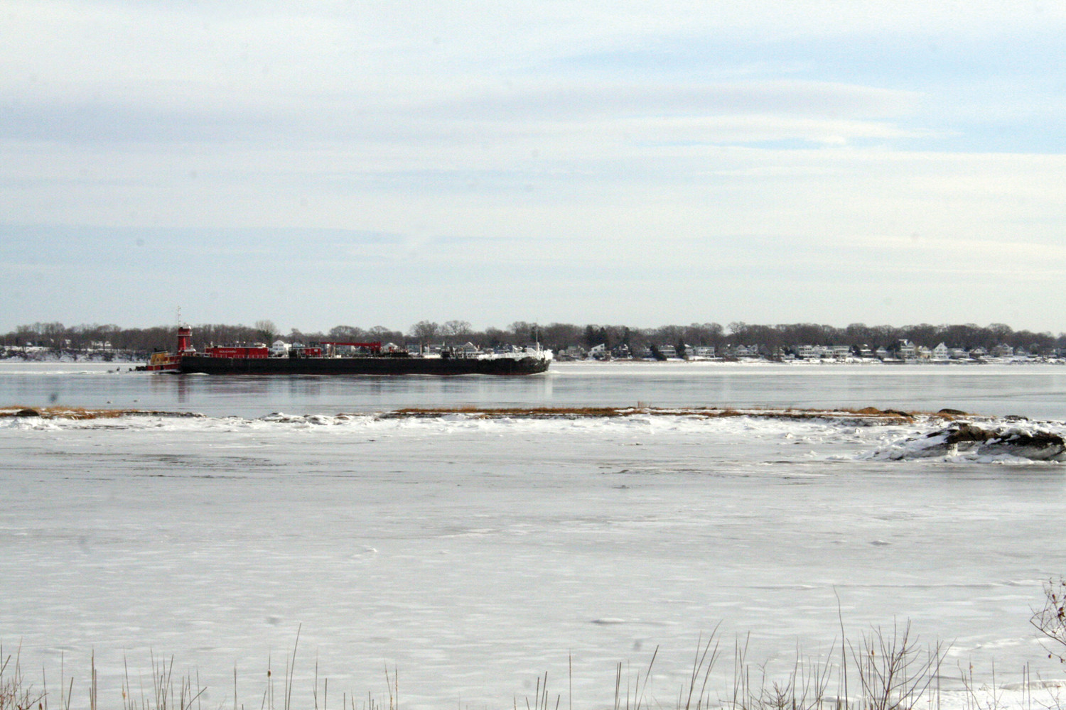 ON THE WAY OUT: A tug and empty barge navigates the Providence River Monday as pictured from Narragansett Parkway.