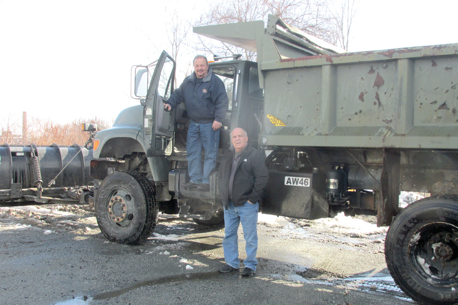 MOUND MOVER: Ben Nascenzi (left), Johnston's Building Inspector, is joined by DPW Director Arnie Vecchione by this huge one-time U.S. Army vehicle that he drove during last week's snow storm. (Sun Rise photo by Pete Fontaine)