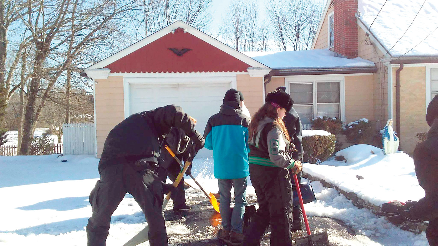 HEAVY LIFTING: Freezing cold temperatures and more than a foot of snow couldn't stop these dedicated explorers from making their rounds throughout town digging out residents who may not have been able to do so on their own. Their dedication was appreciated throughout the community.
