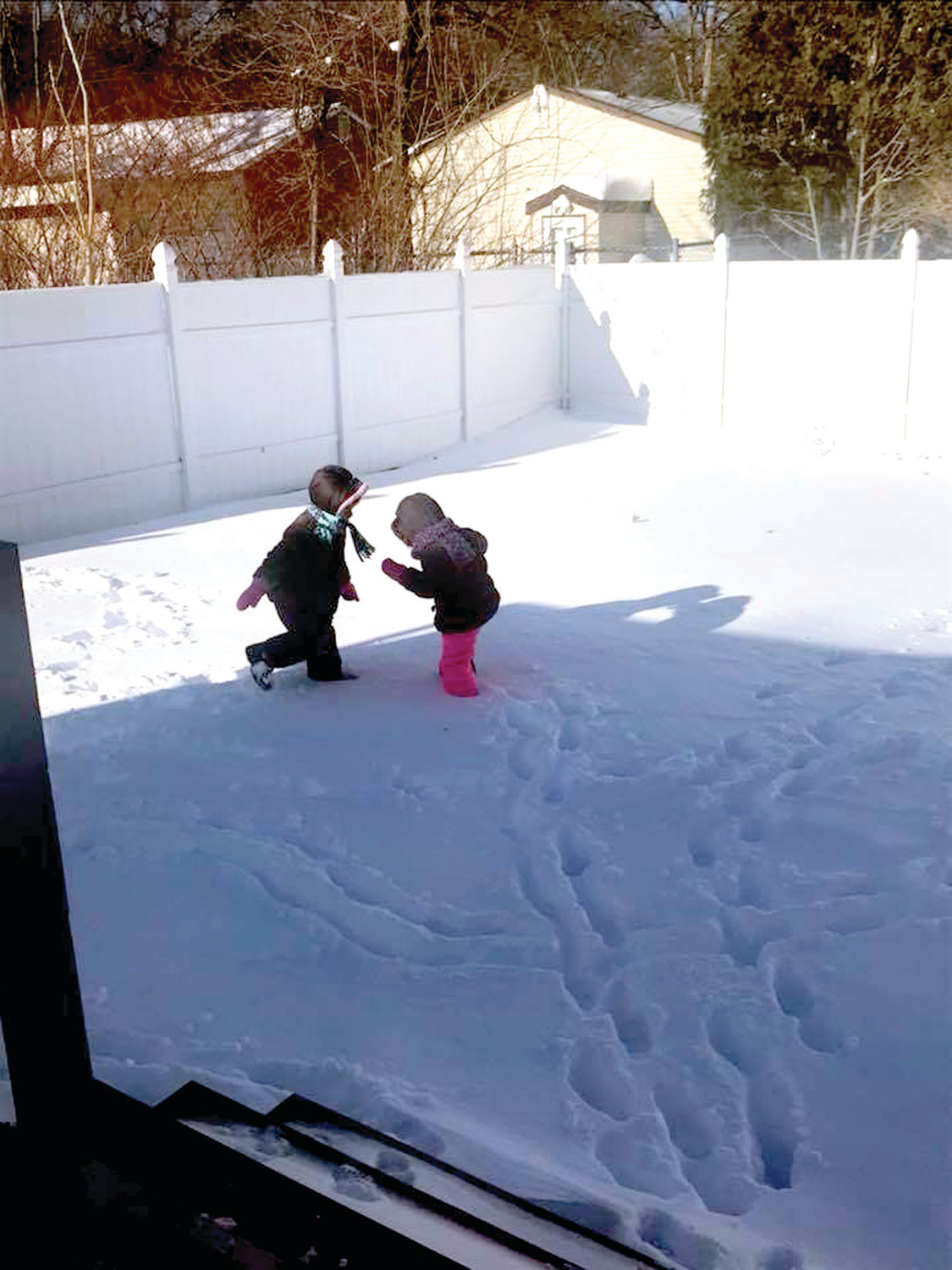 UP TO THEIR KNEES: Ryleigh and Hailey Kimball found fun and more in their backyard following last week's snowstorm. (Submitted photo by Lindsay Smith Kimball)