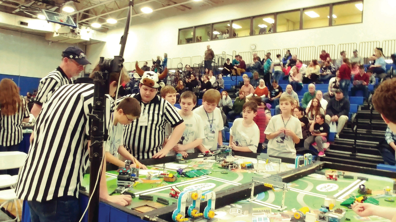 MIXING LEGO AND LOGIC: Tech Tsunami, Evan Franchina Christian Butera (from Warwick), Mark Andraka, Levi Burdon (from Warwick), Blake Sykes, Henry Wind, of Our Lady of Mercy in East Greenwich tally up the score with the referees during Rhode Island Students of the Future's FIRST LEGO League state championship on Saturday, January 13, at Roger Williams University. The team won the 1st place Robot Programming award for the code that used logic blocks to improve reliability and repeatability.